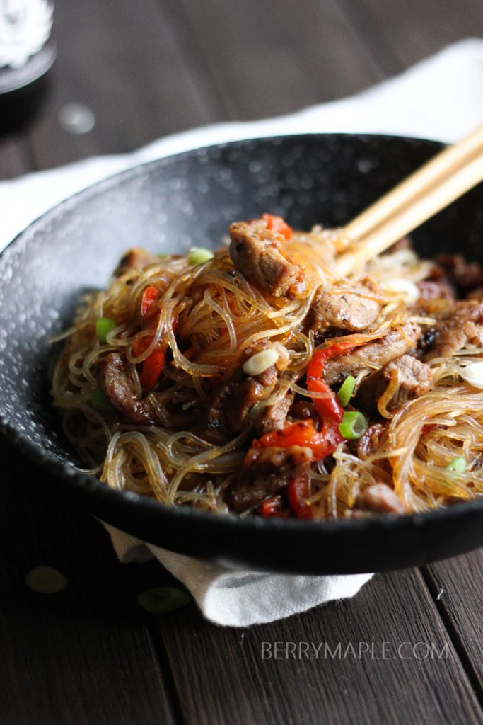 a bowl of clear noodles pork stir fry