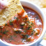red tomato salsa in a small bowl with a chip dipped