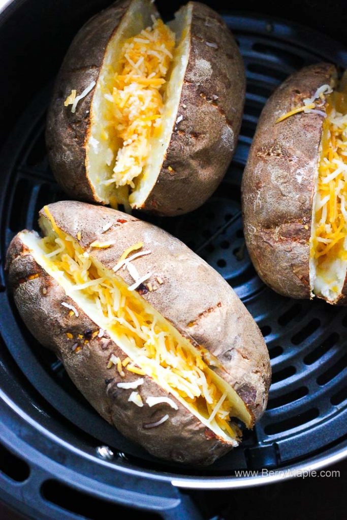 three potatoes with shredded cheese in air fryer