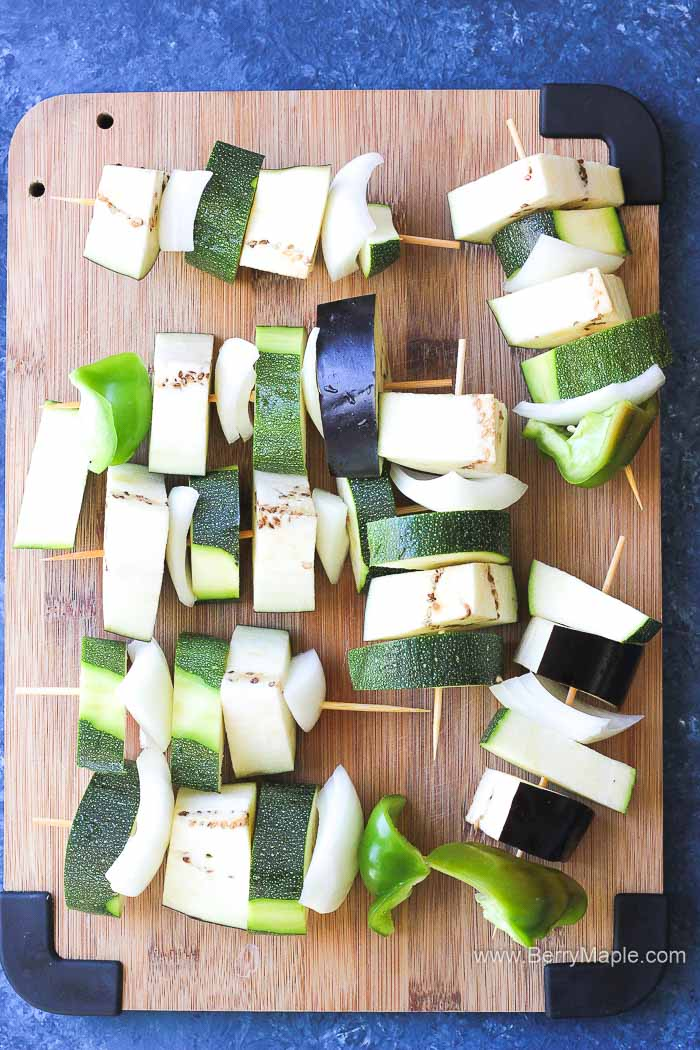 raw veggie skewers on a cutting board