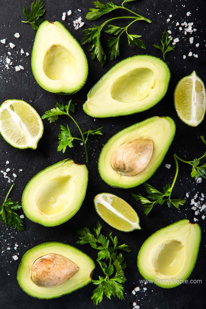 avocado, lime and parsley on black background, top view