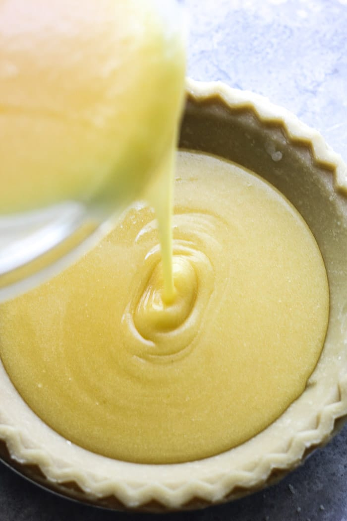 pouring chess pie batter into the pie shell