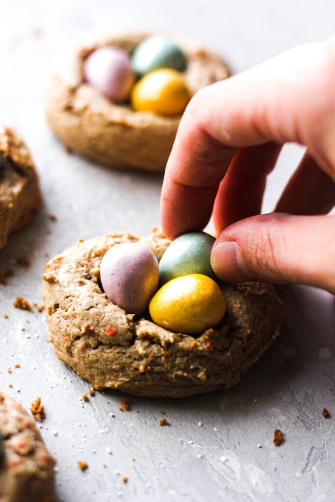 adding candies to easter nest cookies