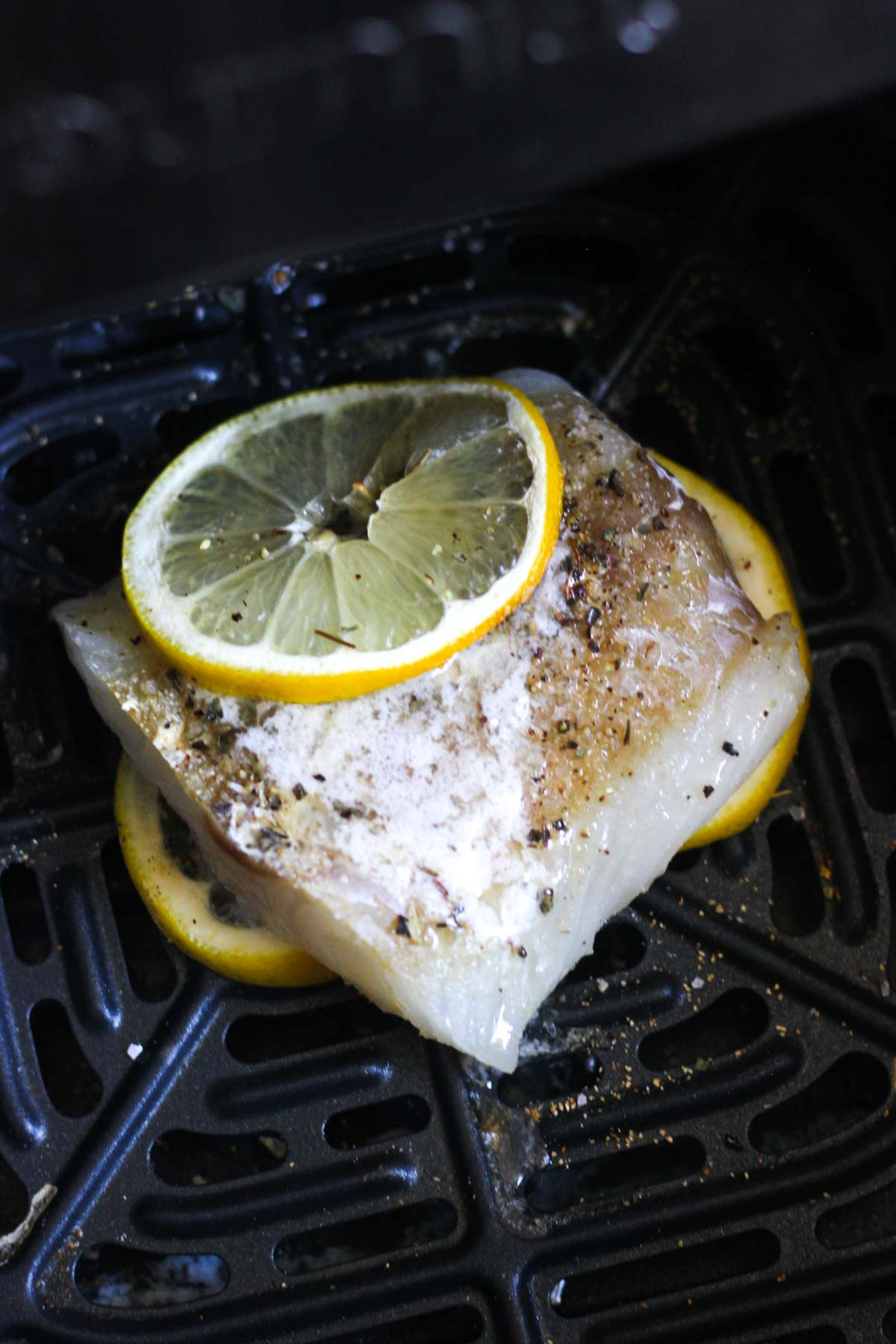 small piece of white cod fish with lemon and black pepper on top