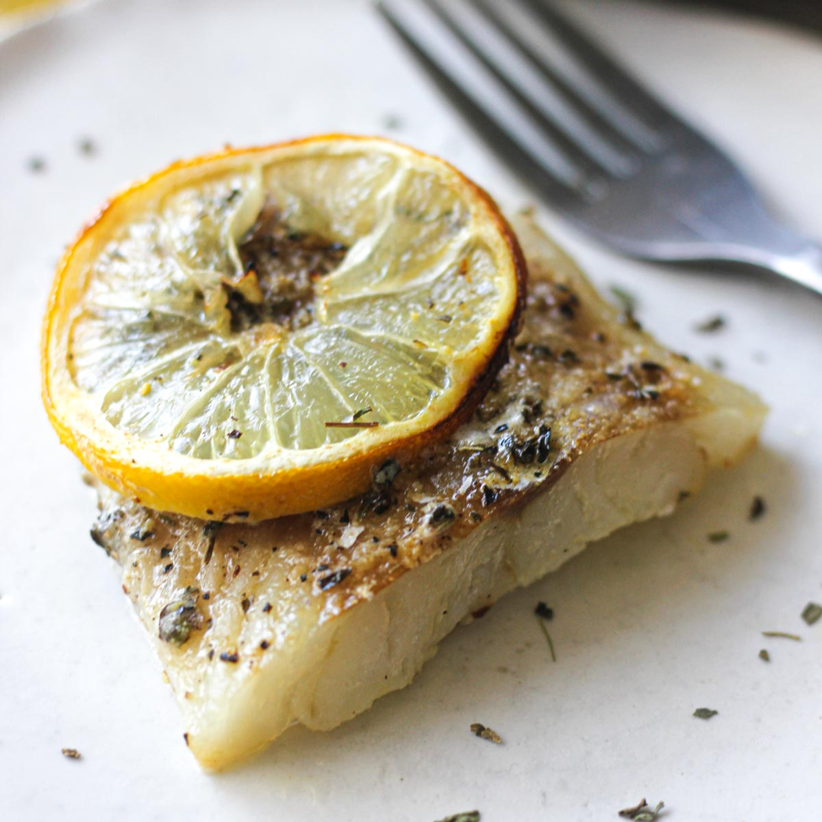 close shot of a cooked cod fillet with a lemon slice on top