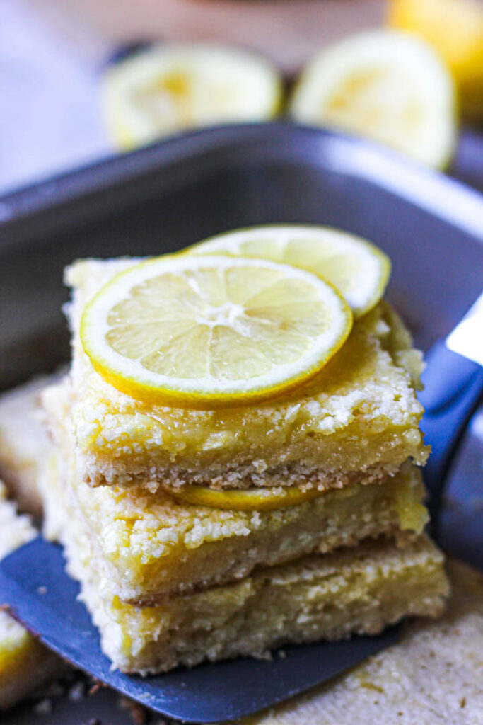 a stack of lemon bars with lemon slices on top