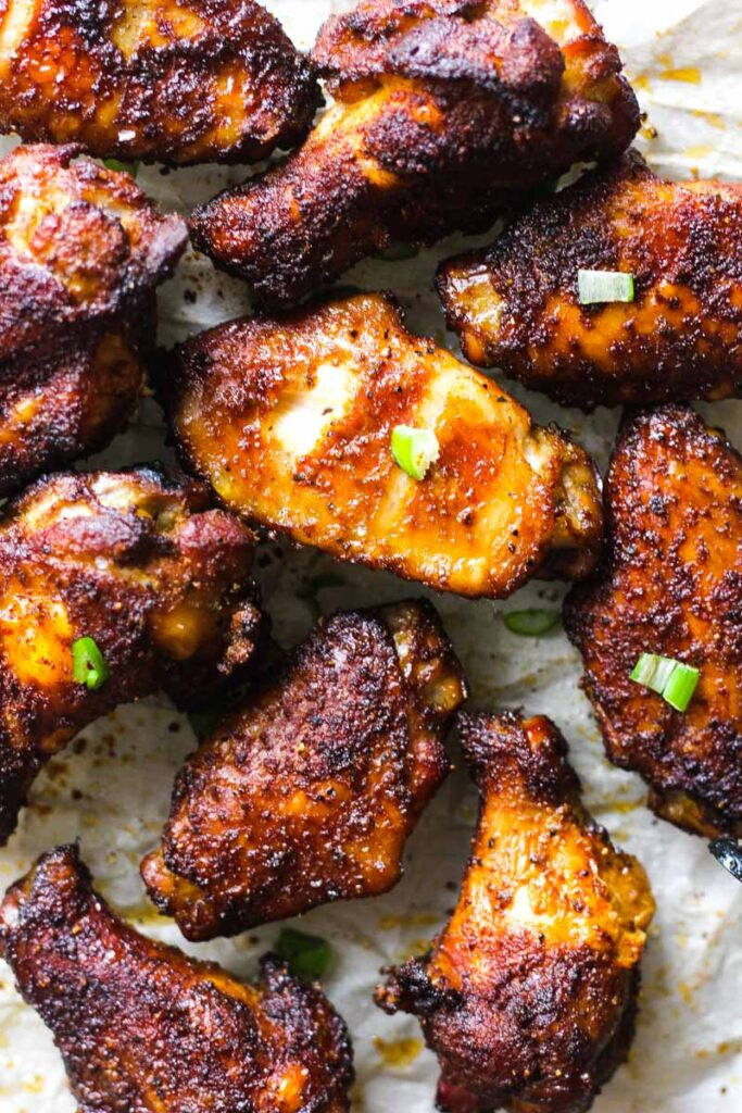 smoked browned wings top view with green onions on a parchment paper