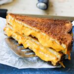 close shot of crunchy golden brown grilled cheese sandwich on a parchment paper