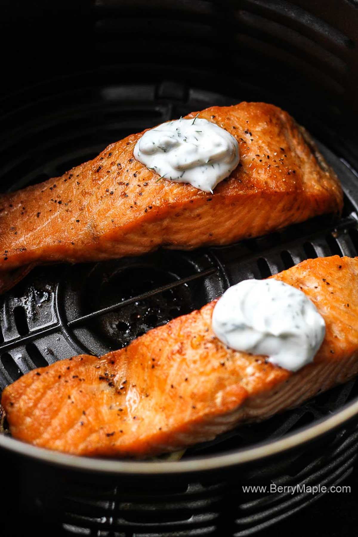 two pieces of salmon in black air fryer basket