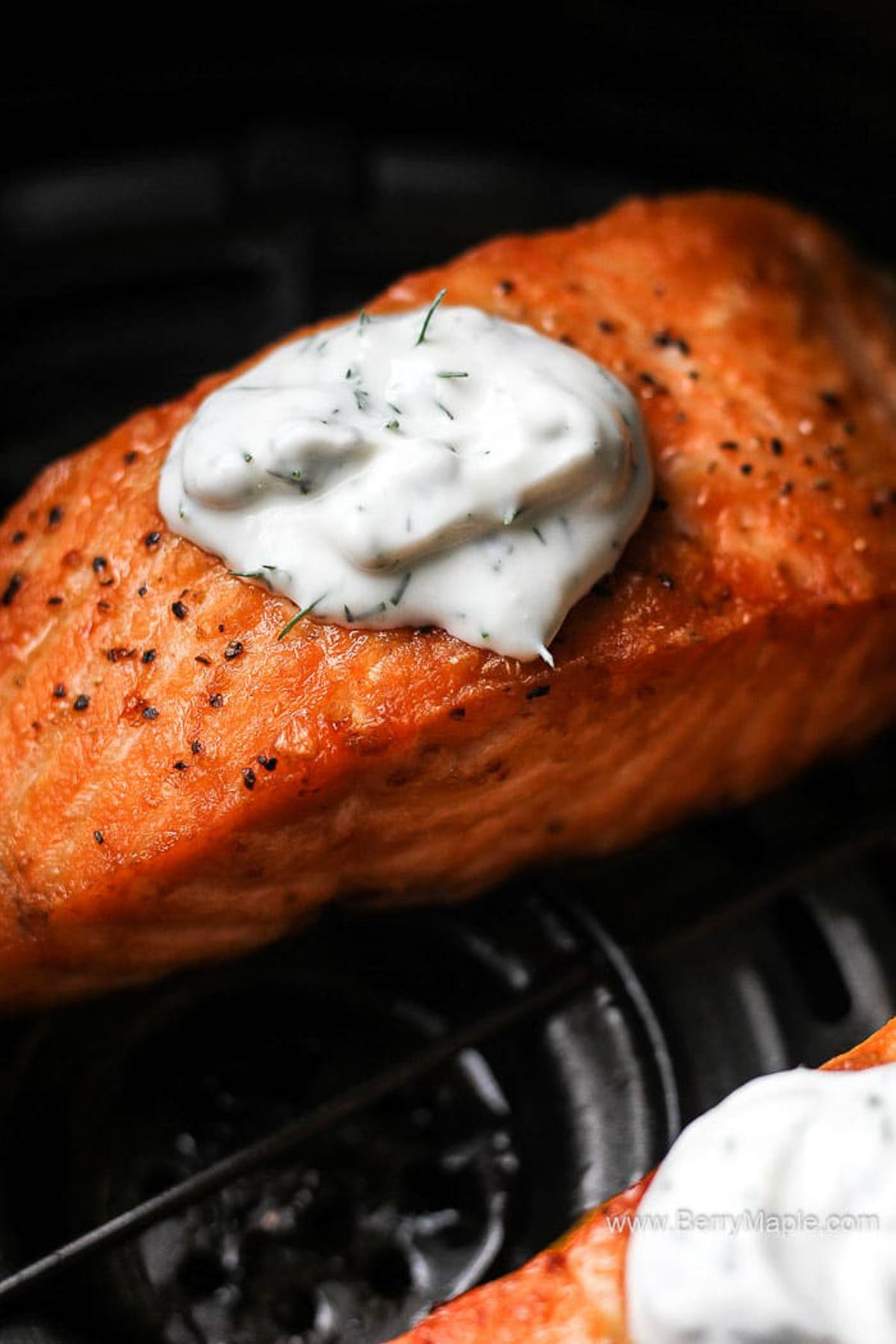close shot of red fish with white sauce on top