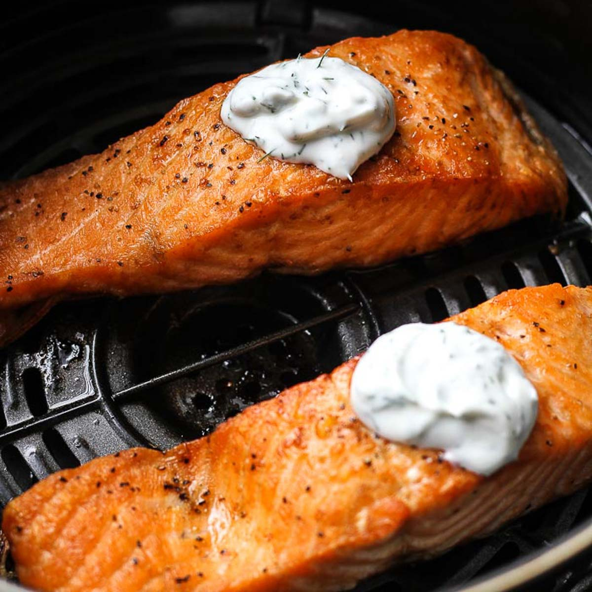 two cooked salmon fillets with white sauce on top in air fryer