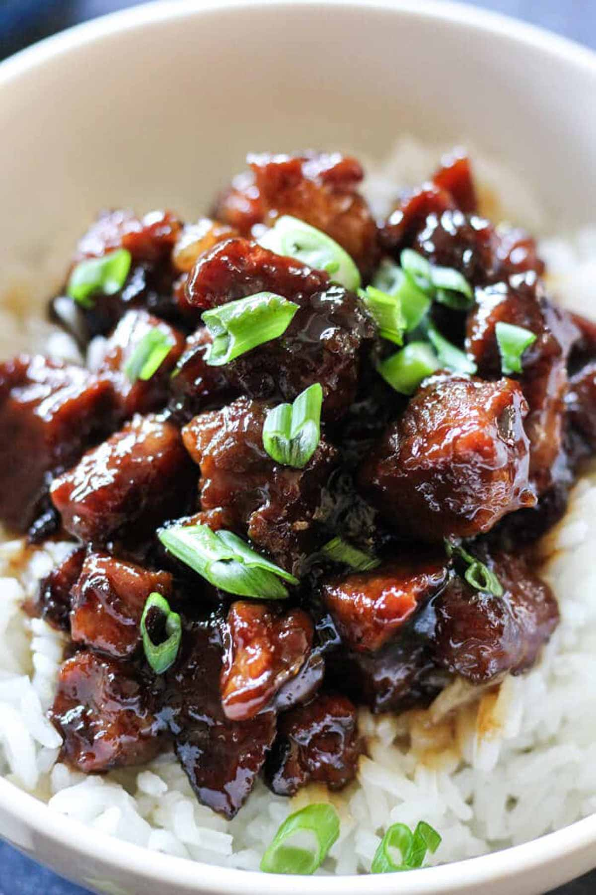 close shot of caramelized sticky meat on top of white rice