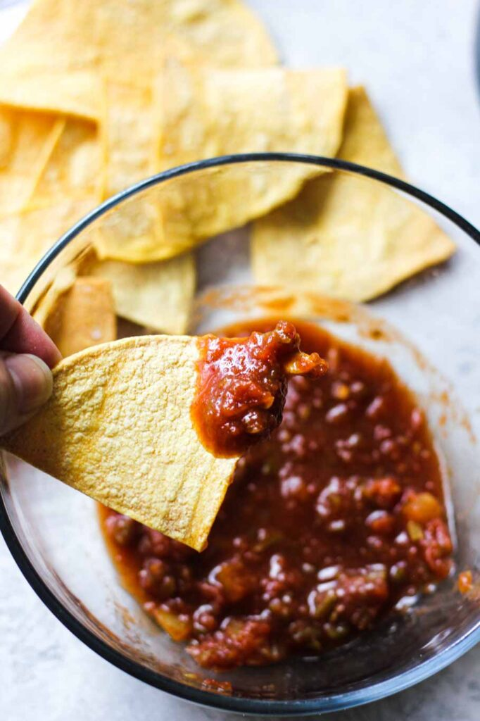 tortilla chip with red salsa in the hand