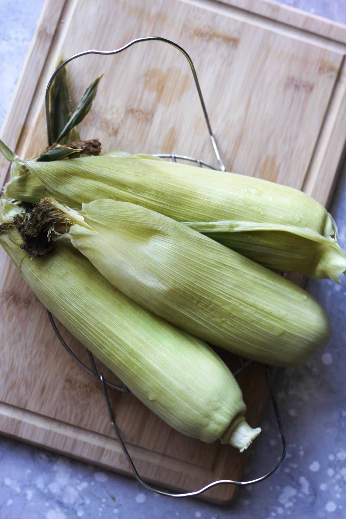 top view of three cooked corn on the cob in husk