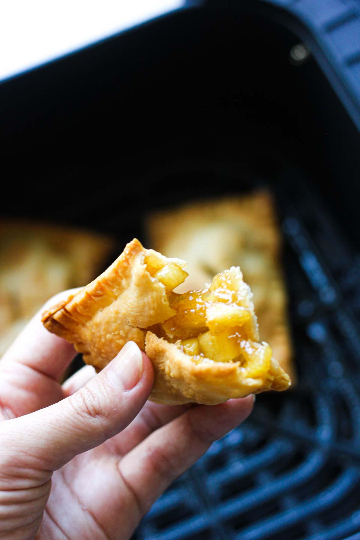 fried mini apple pie in hand