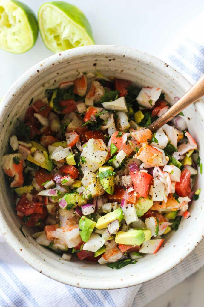 chopped avocado, onions, tomato, cilantro, shrimp and crab in a bowl